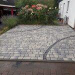 pkw-stellplatz aus betonsteinpflaster mit zwei ornamentalen basaltpflaster-streifen