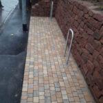 kleine pflasterflaeche aus schoenem betonsteinpflaster vor sandsteinmauer, trockenmauer, bruchsteinmaer