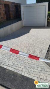 Herstellen einer Garagen-Zufahrt mit Pflastersteinen und Hangabfang mit Mauerwinkel
