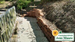 Weg aus Betonplatten und Stützmauern aus Sandstein